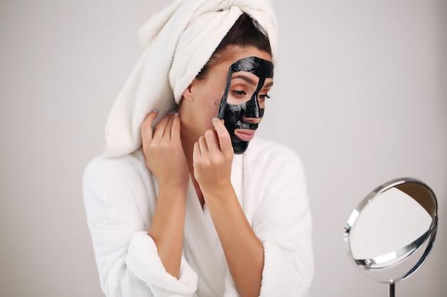 De mooie vrouw verwijdert een reinigingsmasker van haar gezicht