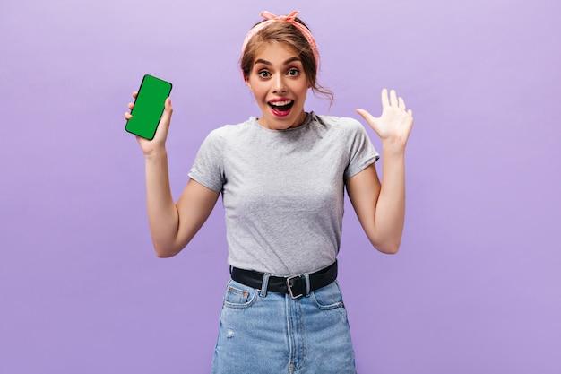 De mooie vrouw vormt gelukkig met smartphone. blij jong meisje in grijze stijlvolle t-shirt en denim rok poseren op geïsoleerde achtergrond.