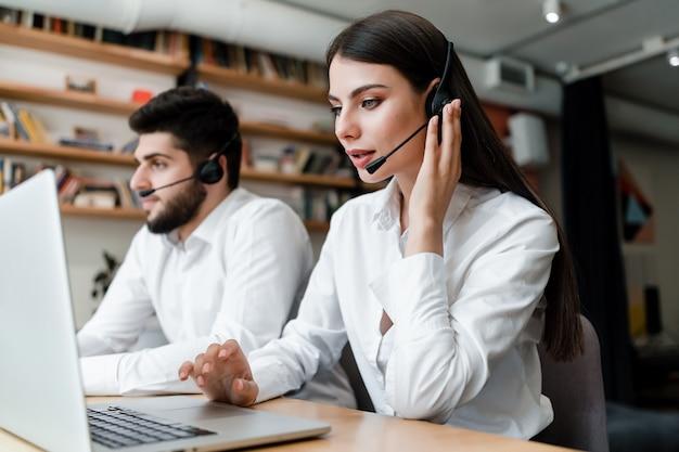 De mooie vrouw werkt in call centre met hoofdtelefoon die cliënttelefoongesprekken beantwoordt