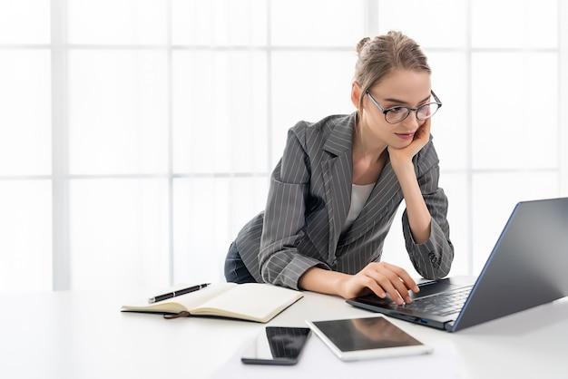 De mooie vrouw werkt thuis met haar laptop. de vrouw draagt een bril en een grijs pak.