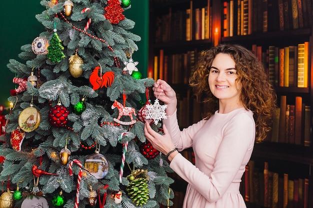 De mooie vrouw wordt klaar kerstboom die zich in de ruimte bevindt