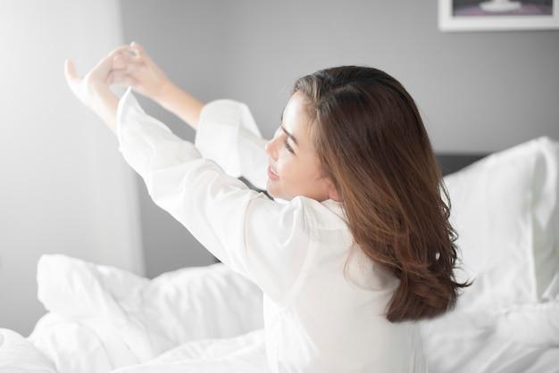 De mooie vrouw wordt op bed in ochtend wakker