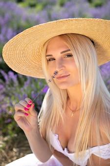 De mooie vrouw zit op lavendelgebied