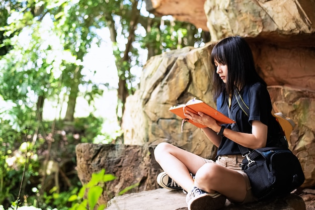 De mooie vrouw zittend op grote rots, schrijven over natuurpad in nationaal park in boek