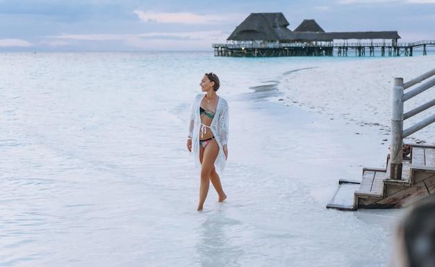 De mooie vrouw zwemt binnen slijtage door de oceaan