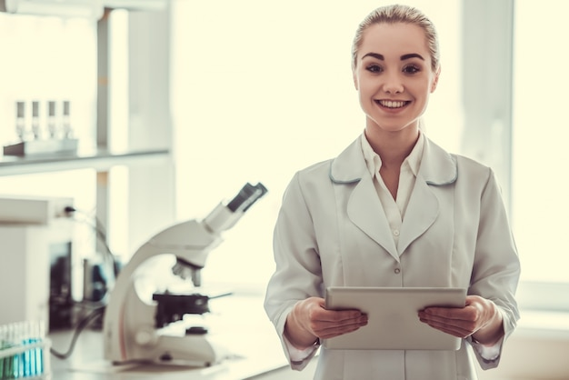 De mooie vrouwelijke arts gebruikt een digitale tablet.