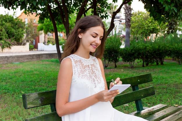 De mooie vrouwelijke student schrijft haar ideeën en gedachten in de notitieboekjezitting op de bank in het park