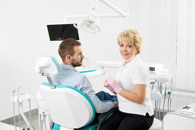 De mooie vrouwelijke tandarts bekijkt de camera die medische instrumenten houdt en is klaar om de tanden van jonge mannelijke cliënt van de tandheelkunde te genezen.