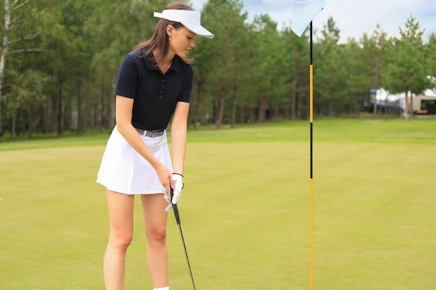 De mooie vrouwengolfspeler treft voorbereidingen om op bal op de groene golfbaan te schieten.