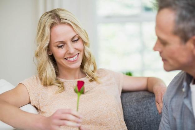De mooie vrouwenzitting op haar laag en echtgenoot die een roos in het leven aanbieden nam toe