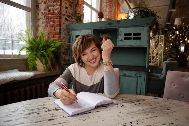 De mooie, zakelijke, succesvolle, volwassen vrouw zit in een café met een notitieboekje en een pen.