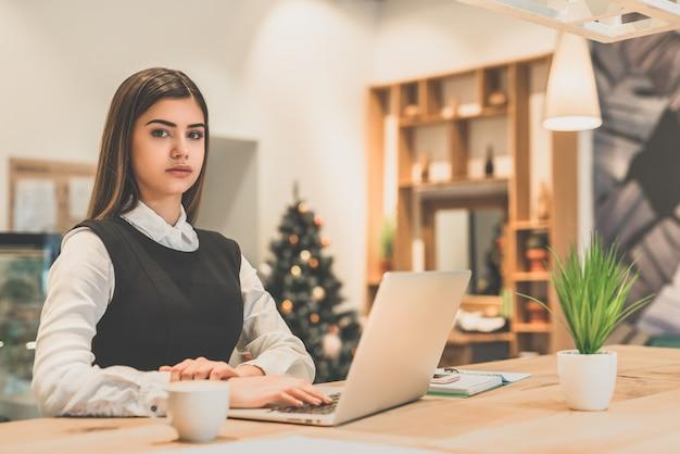 De mooie zakenvrouw die met een laptop werkt