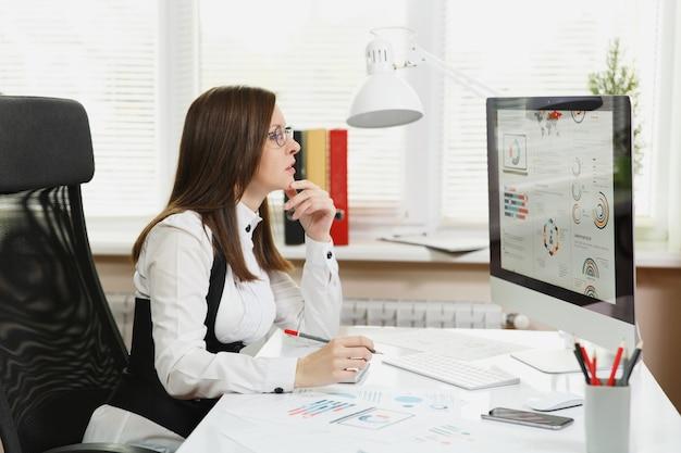 De mooie zakenvrouw in pak en bril die op de computer werkt met documenten in een licht kantoor, kijkend naar de monitor