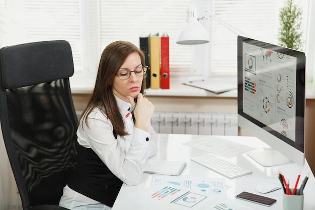 De mooie zakenvrouw in pak en bril die op de computer werkt met documenten in een licht kantoor, kijkend naar de tafel