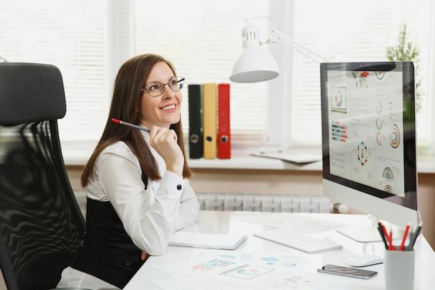 De mooie zakenvrouw in pak en bril die op de computer werkt met documenten in een licht kantoor, opzij kijkend