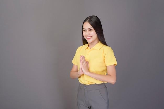 De mooie zelfverzekerde vrouw begroet (thaise wai) om respect over grijs te tonen