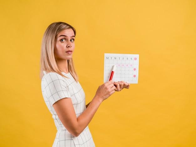 De mooie zijdelingse jonge vrouw met hoed toont kalender