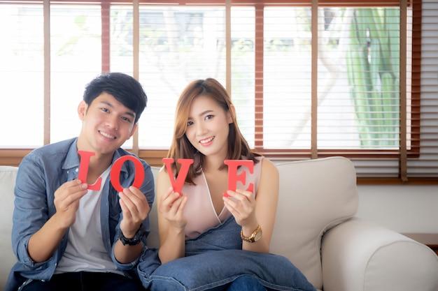 De mooie zitting van het portret jonge aziatische paar op bank