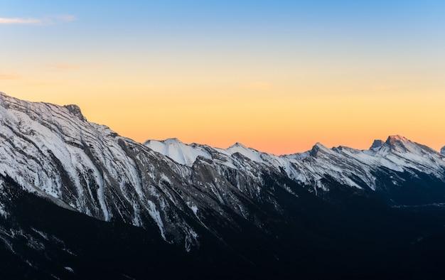 De mooie zonsondergangmening van sneeuw dekte rotsachtige bergen af bij het nationale park van banff in alberta, canada.