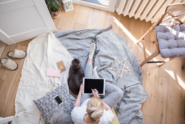 De mooie zwangere bedrijfsvrouw gebruikt een digitale tablet, bekijkt camera en glimlacht terwijl thuis status dichtbij haar werkende plaats