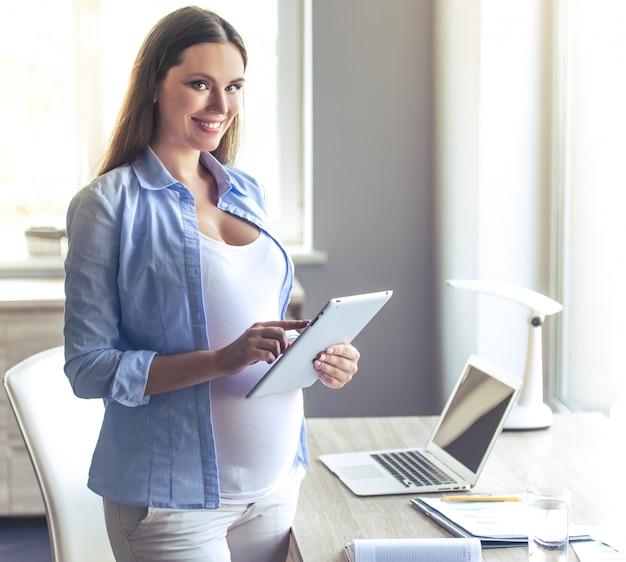 De mooie zwangere bedrijfsvrouw gebruikt een digitale tablet.