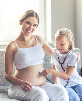 De mooie zwangere vrouw bekijkt camera en het glimlachen.