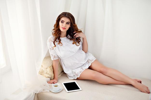 De mooie zwangere vrouw gebruikt thuis een digitale tablet terwijl het zitten op de laag