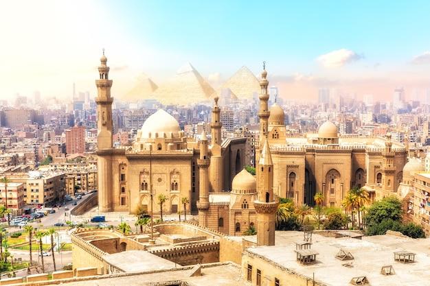 De moskee-madrassa van sultan hassan en de piramides op de achtergrond, prachtig uitzicht over caïro, egypte.