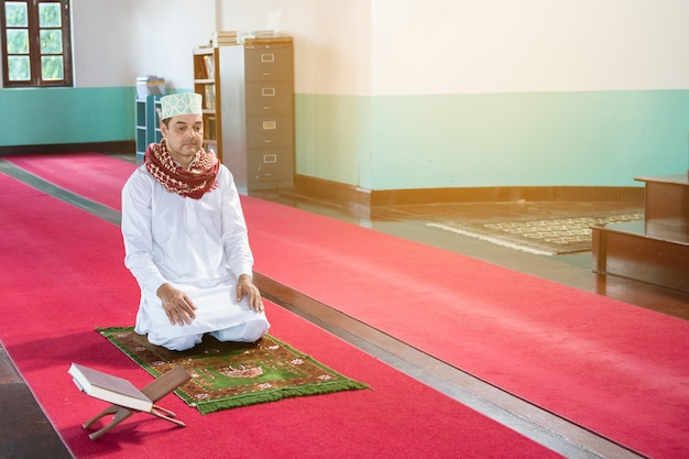 De moslim arabische zakenman zit op zijn knieën met witte hijabkleding