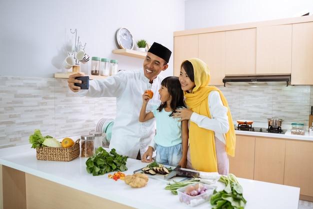 De moslim aziatische familie neemt selfie tijdens de voorbereiding van het iftardiner samen thuis