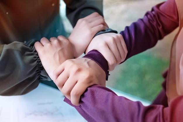 De moslimhanden raken elkaar, medewerker, unie, teken en symbool van kracht en succes, wazig licht rondom