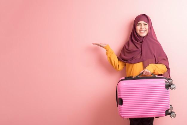 De moslimvrouw met hijab houdt bagage op roze achtergrond, reizen de mensen concept