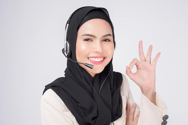 De moslimvrouw van de klantenserviceexploitant in kostuum die hoofdtelefoon over witte achtergrond draagt studio