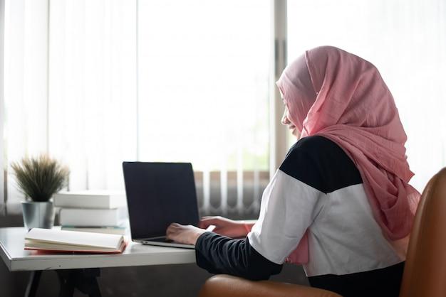 De moslimvrouw zittend op een houten stoel, thuis werkend, met behulp van laptop en boeken op een houten bureau, naast het raam,