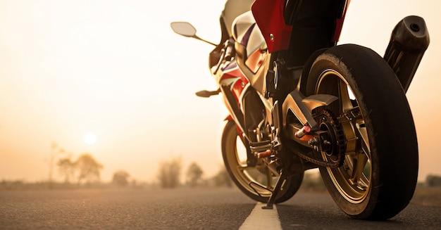 De motorfiets die op de wegrechterkant en de zonsondergang parkeren