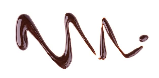 De motregen van de chocoladesiroop op wit wordt geïsoleerd dat