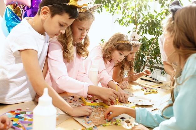 De mozaïekpuzzelkunst voor kinderen, creatief spel voor kinderen. de handen spelen mozaïek aan tafel. close-up van kleurrijke veelkleurige details. creativiteit, ontwikkeling van kinderen en leerconcept