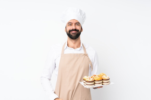 De muffincake van de jonge mensenholding over het geïsoleerde witte muur lachen