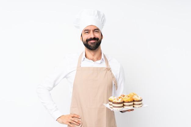 De muffincake van de jonge mensenholding over het geïsoleerde witte stellen met wapens bij heup en het glimlachen