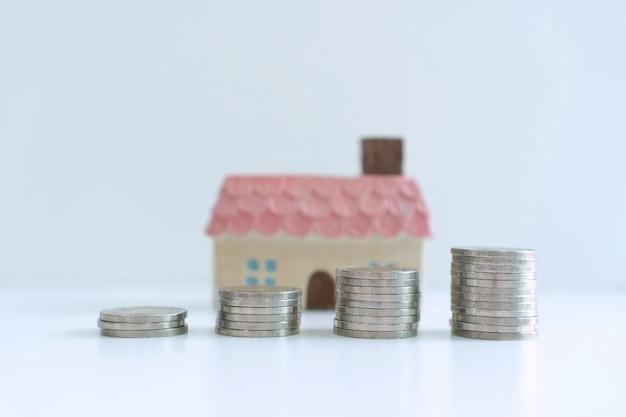 De muntstukkenstapel voor besparingsgeld op witte achtergrond, besparingsplannen voor huisvestings financieel concept, sluit omhoog