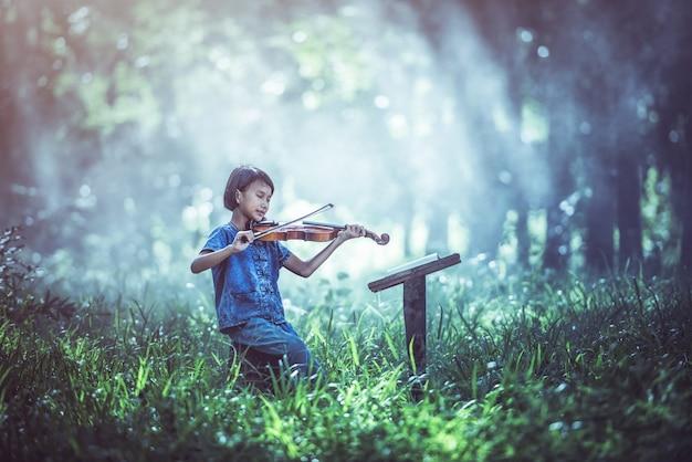 De musical: klein aziatisch kind dat viool speelt in de open lucht