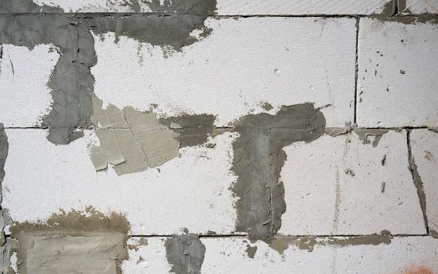 De muur is gemaakt van witte kalkzandsteen witte bakstenen metselwerk macro verouderde bakstenen muur