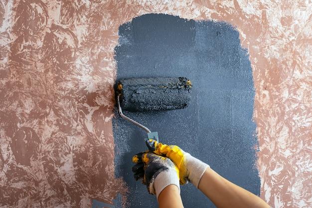 De muur schilderen met een roller grijze verf.