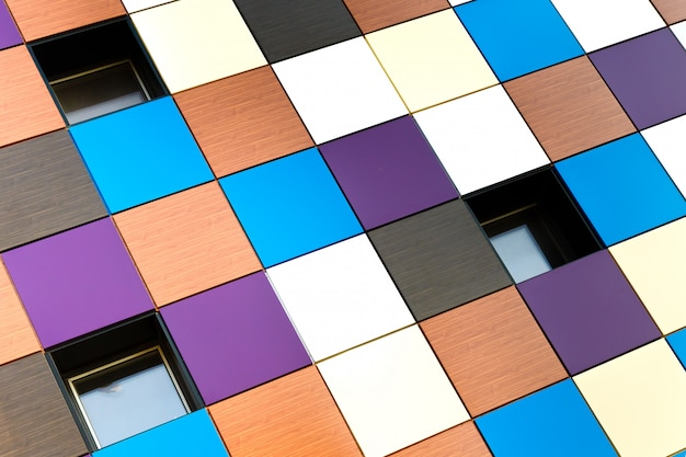 De muur van het gebouw bestaat uit veelkleurige vierkante panelen