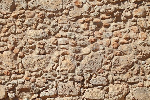 De muur van oud beige steenmetselwerk.