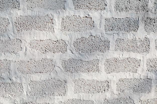 De muur van sintelblokken is wit geverfd. structuur