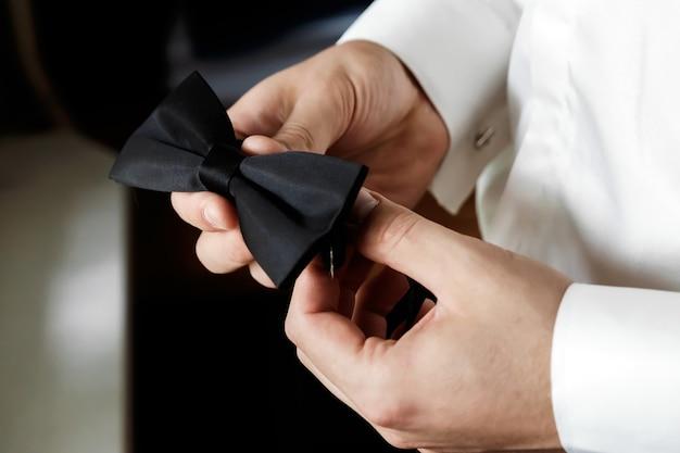 De muzhchin, een wit shirt met een grote en donkere stijlvolle broek, heeft een vlinderstrik