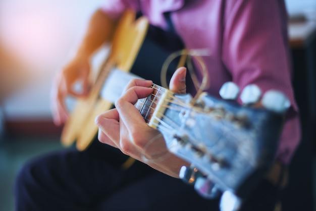 De muzikant geniet van de gitaar. focus op vingers
