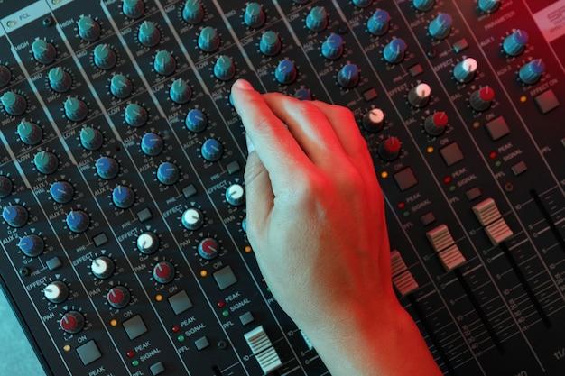 De muzikant past het geluid aan op de audiomixer