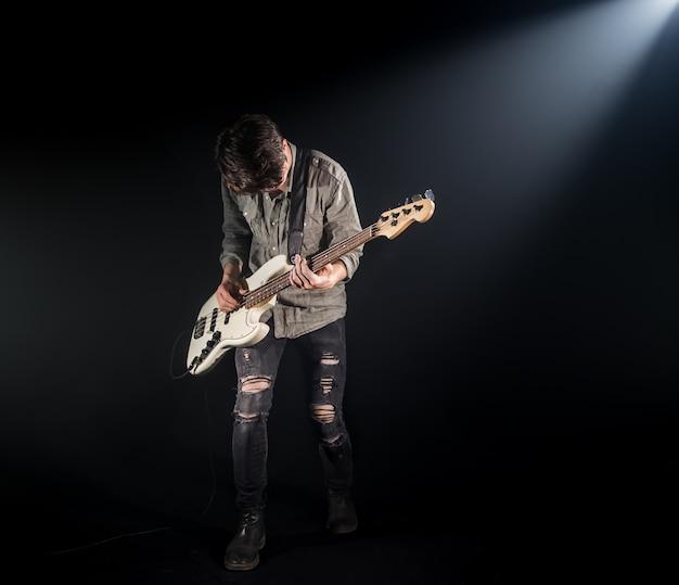 De muzikant speelt basgitaar, op een zwarte achtergrond met een lichtstraal